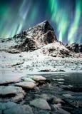 Van Aurora Borealis (Noordelijke lichten) de explosie over bergen in gl stock foto's