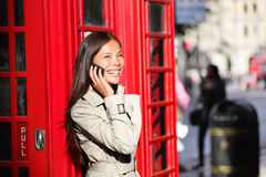 Van bedrijfs Londen vrouw op slimme telefoon door rode cabine Stock Fotografie