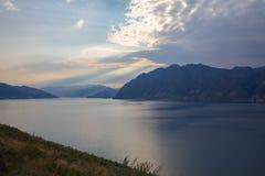 Van bewolkte aan zonnige hemel over de bergen en het water royalty-vrije stock afbeeldingen