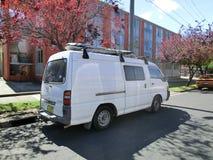 Van blanca parking debajo de un árbol en otoño fotografía de archivo libre de regalías