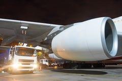 Van brandstof voorziend een reusachtig vliegtuig, verbond een vrachtwagen met brandstof met slangen met een brandstoftank, een vl royalty-vrije stock afbeelding