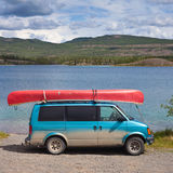 Van with Canoe. Dirty blue minivan with red canoe on roofrack Royalty Free Stock Image