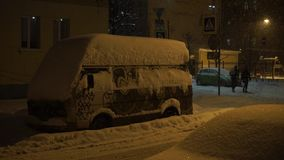 Van is covered with snow. Heavy snowfall in the city at night. stock video footage