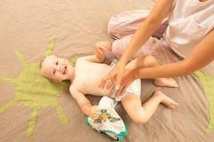 Van de de babyjongen van de mammaverandering grappige de zuigelingsluier stock foto