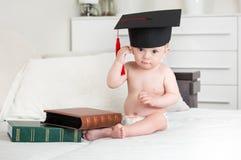 10 van de babymaanden oud jongen die op bed met boeken situeren en g opstijgen Stock Afbeelding