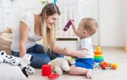 10 van de babymaanden oud jongen die stuk speelgoed tonen mobiele telefoon aan zijn moeder Royalty-vrije Stock Foto's
