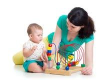 Van de babymeisje en moeder spel met onderwijsstuk speelgoed Stock Foto