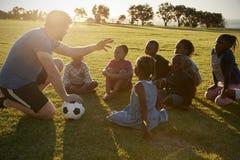 Van de basisschooljonge geitjes en leraar zitting met bal op gebied Royalty-vrije Stock Afbeelding