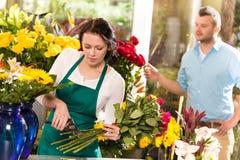 Van de bloemist de scherpe bloemen van de vrouw man van het de winkelboeket Stock Foto's