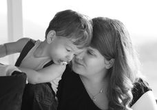 Van de close-up houdende van moeder en zoon het fluisteren geheimen in oren stock foto