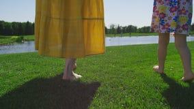 Van de close-upmamma en dochter benen die op gras lopen stock footage