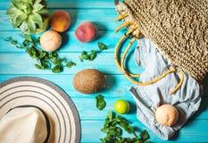 Van de de achtergrond zomervakantie thema met zak, hoed, kokosnoot, zonnebril en Perziken op blauwe houten achtergrond stock afbeeldingen
