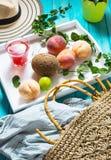 Van de de achtergrond zomervakantie thema met zak, hoed, kokosnoot, zonnebril en Perziken op blauwe houten achtergrond royalty-vrije stock foto