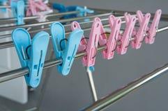 Van de de doekkleur van de klemmenhanger het blauwe roze plastic concept Stock Afbeeldingen