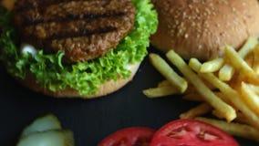 Van de de grillfrieten ingelegde komkommer van de rundvleeshamburger de tomatenkaas stock video