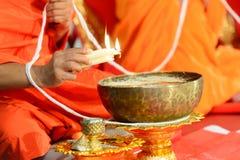 Van de de hand gietende smelting van de boeddhistische monnik de kaarsscheuren aan het water voor het maken van zegenwater royalty-vrije stock fotografie