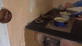 Van de de handencontrole van de dorpsbewonervrouw de kokende aardappels op oud ovenfornuis 4K stock videobeelden