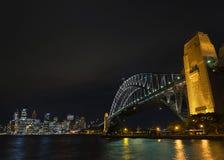 Van de de havenbrug en horizon van Sydney oriëntatiepunten in Australië bij nigh Stock Fotografie
