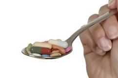 Van de de holdingslepel van de hand de verschillende kleurrijke pillen wih Stock Afbeelding