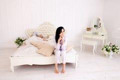 Van de de kerelochtend van het meisjeskielzog het witte bed in ruimte Royalty-vrije Stock Fotografie