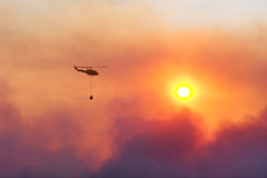 Van de de reddingshelikopter van de brand de bevochtigingsbrand tegen zonsondergang Stock Foto's