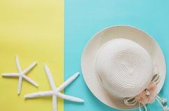 Van de de zomervakantie minimaal concept als achtergrond Strohoed, zeesterren Royalty-vrije Stock Afbeeldingen