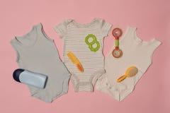 Van de drie babybodysuit en zorg toebehoren op een roze achtergrond Klerenconcept stock foto's