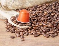 In van de forground Houten lepel en koffie capsule dichte omhooggaand royalty-vrije stock foto