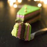 Van de framboos-pistache de plakken operacake met met groene spiegelglans worden verfraaid op zwarte lichten dat als achtergrond  royalty-vrije stock afbeeldingen