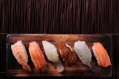 Van de het dienbladmening van het sushi Japanse voedsel diverse houten de bodemgrens met platte kop stock afbeelding