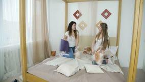 Van de het hoofdkussenstrijd van de vrienden onbezorgde vrije tijd de meisjesomhelzingen stock video