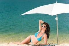 Van de het strandvrouw van de zomer de blauwe bikini onder parasol royalty-vrije stock afbeelding