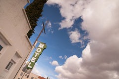 Van de het Teken de Duidelijke Blauwe Hemel van het neonmotel Witte Golvende Wolken royalty-vrije stock afbeelding
