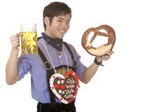 Van de holdingsOktoberfest van de mens het bierstenen bierkroes en Pretzel Royalty-vrije Stock Foto