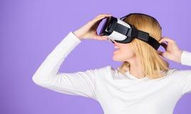 Van de hoofdtelefoonglazen van de vrouwengreep vr de violette achtergrond Digitaal apparaat en moderne kansen Virtuele werkelijkh stock foto's