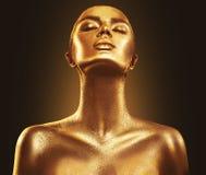 Van de de huidvrouw van de manierkunst gouden het portretclose-up Goud, juwelen, toebehoren Modelmeisje met gouden glanzende make Stock Foto's