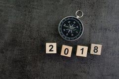 Van de jaar 2018 voorspelling of richting concept met kompas en woode stock fotografie