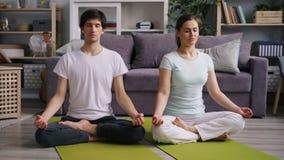 Van de jongerenmeisje en kerel het ontspannen in lotusbloem stelt met gesloten ogen na yoga stock video