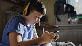 8 van de Kaukasische typejaar jongen die smartphone spelen thuis stock video