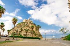 Van de kerksanta maria van het kloosterheiligdom dell Isola bovenop rots van Thyrreense Zee en groene palmen, blauwe hemel met wi stock afbeeldingen