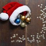 Van de Kerstmisballen en Kerstman hoed op houten achtergrond Stock Foto