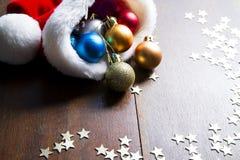 Van de Kerstmisballen en Kerstman hoed op houten achtergrond Royalty-vrije Stock Afbeelding