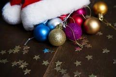 Van de Kerstmisballen en Kerstman hoed op houten achtergrond Stock Afbeeldingen
