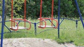 Van de de kinderjarenaantrekkelijkheid van de schommelingsspeelplaats verlaat de het gras groene aard de de stammenzomer van de a stock video