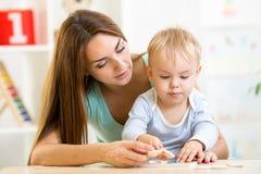 Van de kindjongen en moeder spelstuk speelgoed thuis Stock Fotografie