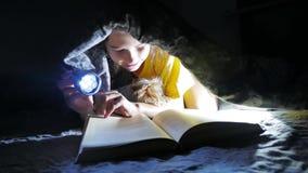 Van de kindtiener en hond het lezingsmeisje leest boek bij nacht die met jong geitjeflitslicht onder een deken liggen stock video