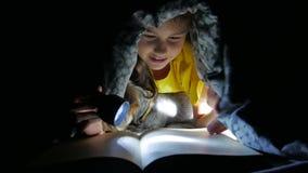 Van de kindtiener en hond het lezingsmeisje leest boek bij nachtjong geitje met flitslicht liggend onder een deken stock videobeelden