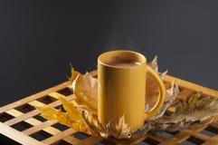 Van de koffiekop en herfst bladeren op een houten lijst Stock Foto's