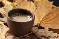Van de koffiekop en herfst bladeren op een houten lijst Royalty-vrije Stock Afbeelding