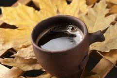 Van de koffiekop en herfst bladeren op een houten lijst Royalty-vrije Stock Foto's